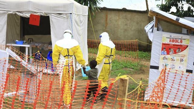 Zwei Ärzte begleiten einen Jungen ins Behandlungszentrum von Beni. Weil die Sicherheitslage Gegenmaßnahmen erschwert, könnte sich die Seuche in der Region etablieren.