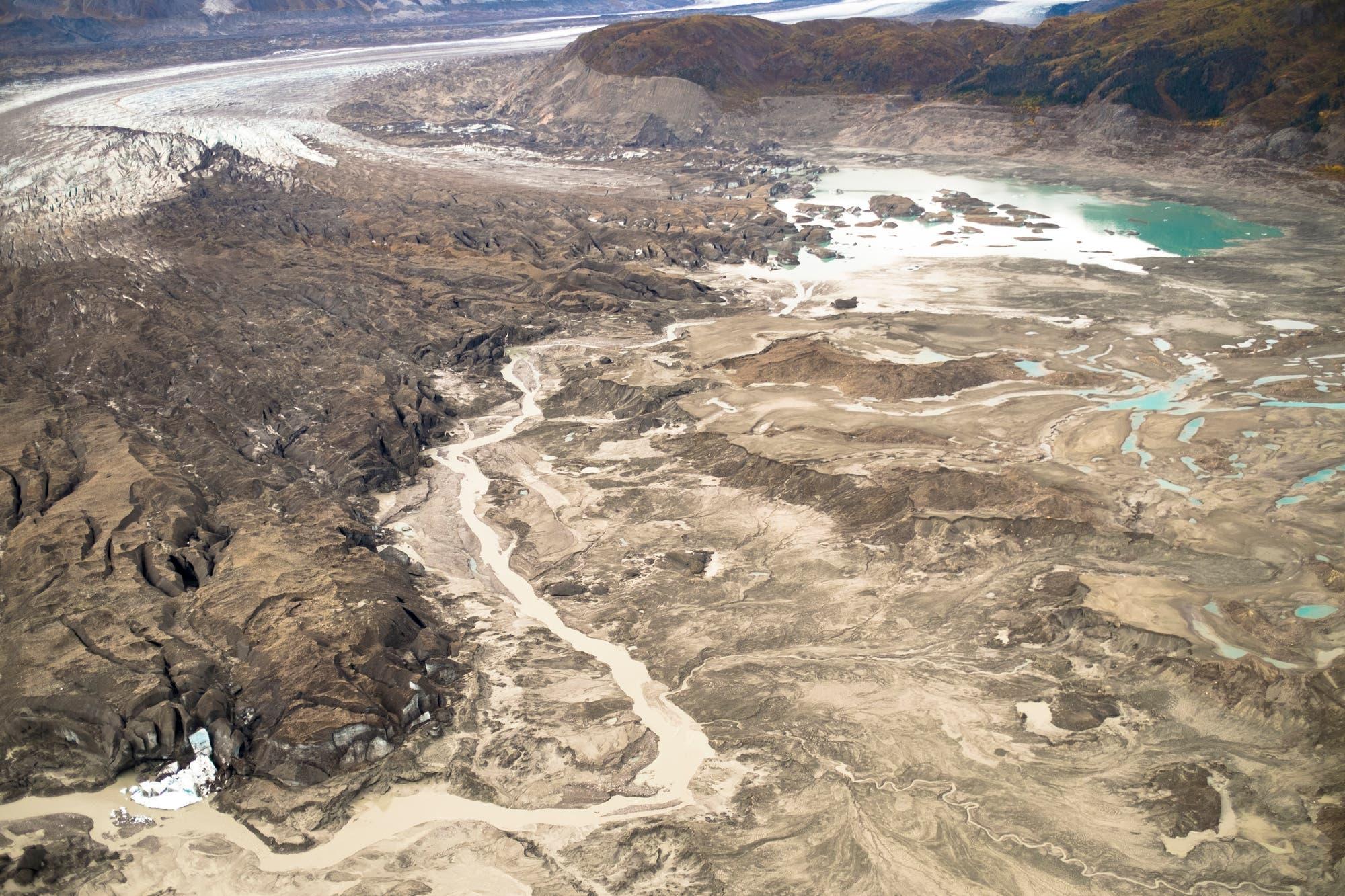 Ein schmaler Kanal kreuzt Ödland vor der Gletscherzunge, das der Gletscher erst kürzlich freigegeben hat.