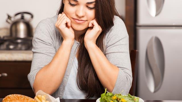Frau mit Salat und Burger