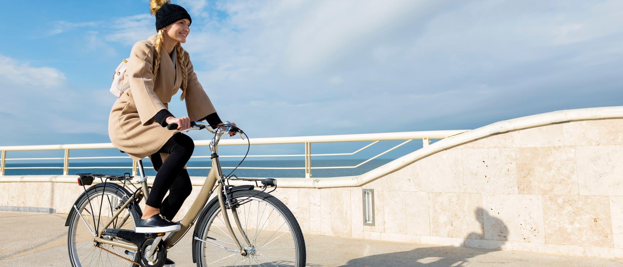 Eine Frau in einem braunen Mantel fährt an einer Strandpromenade Fahrrad.