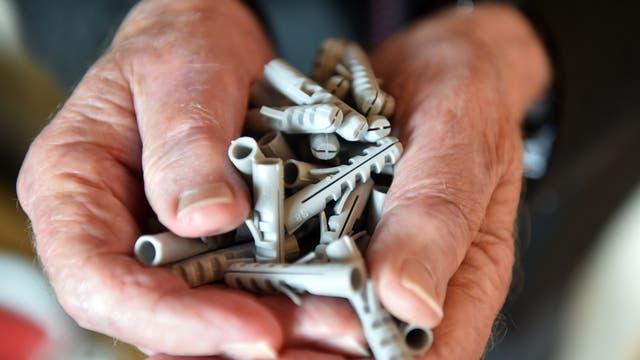 Artur Fischer mit einer Hand voll Dübel