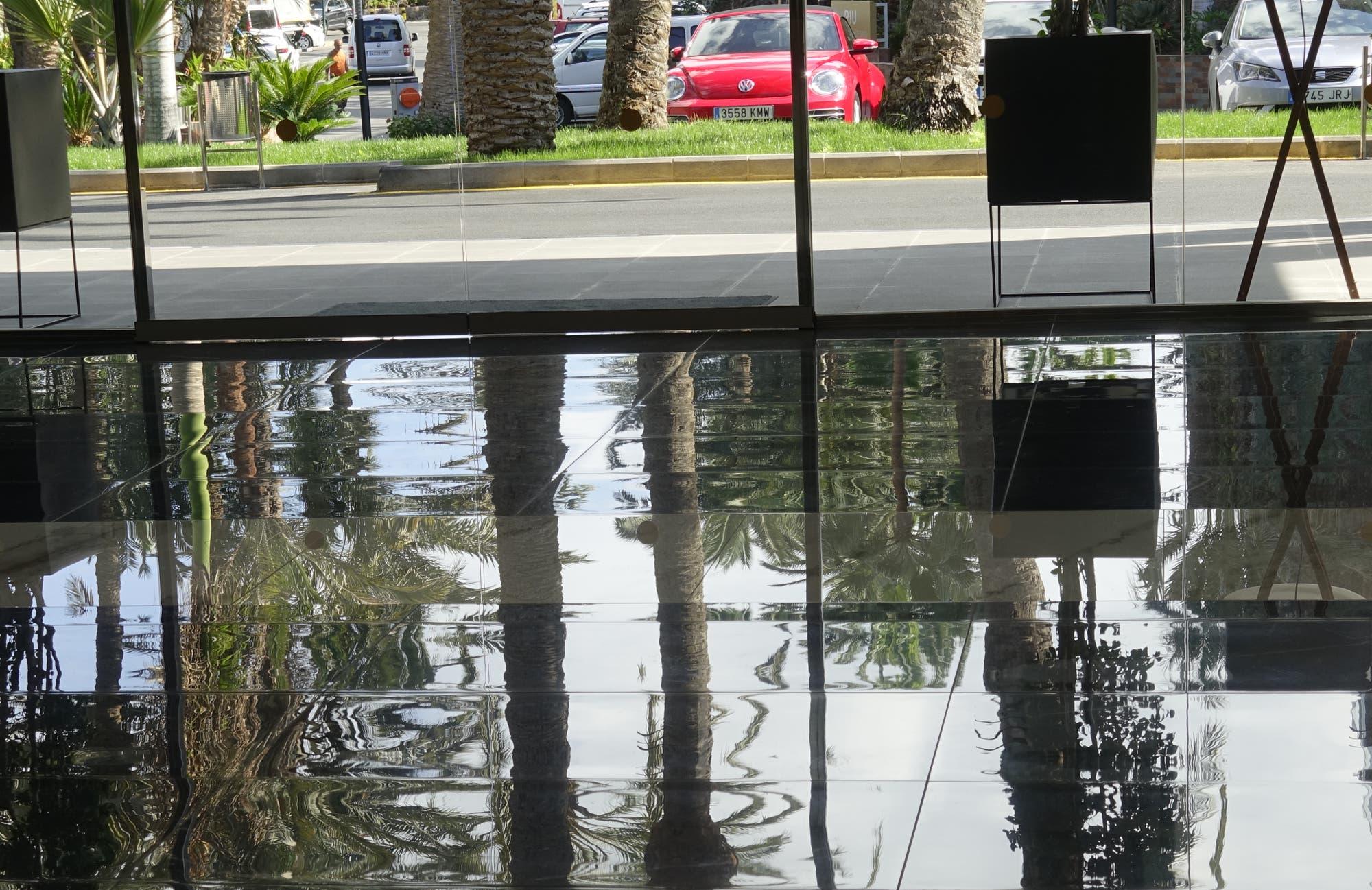 Foto eines glatten Bodens in einem Gebäude, in dem sich die Außenwelt spiegelt