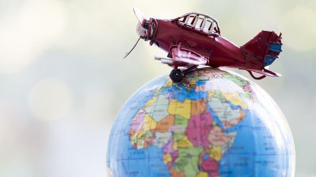 Spielzeugflieger auf einem Globus