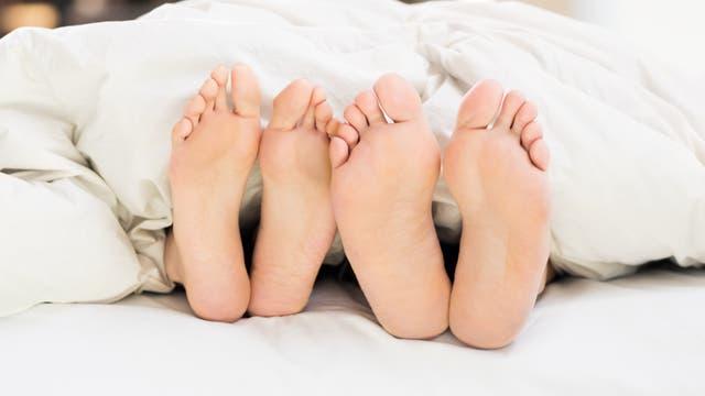 Zwei Paar Füße, die unter einer zu kurzen Bettdecke herausgucken