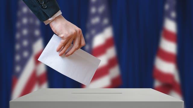Eine Hand wirft einen Zettel in eine Wahlurne. Im Hintergrund drei US-Flaggen