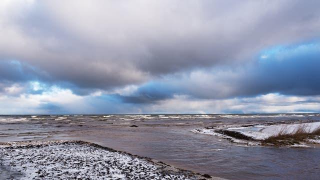 Blick über eine verschneite Küstenlinie aufs Meer