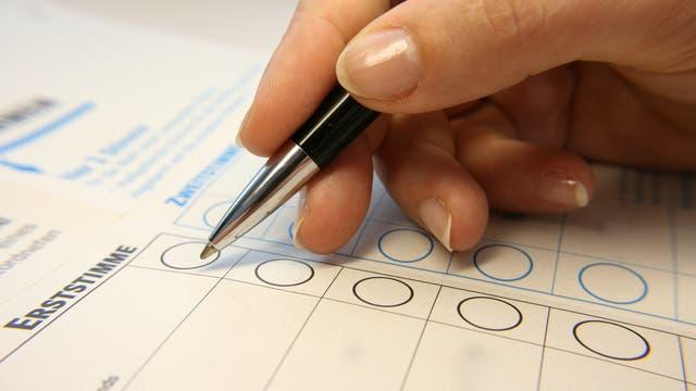 Eine Hand mit Stift kreuzt auf einem Wahlzettel für die Bundestagswahl ein Feld an.