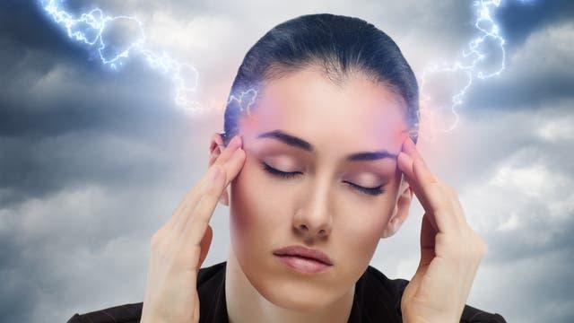 Der Kopf einer leidenden jungen Frau wird mit Blitzen traktiert, um ihr zu helfen