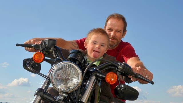 Junge mit Down-Syndrom auf Motorrad