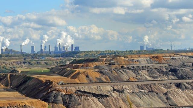 Der Braunkohletagebau bei Garzweiler mit Kraftwerken im Hintergrund.