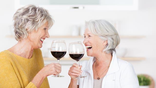 Zwei ältere Frauen trinken Rotwein