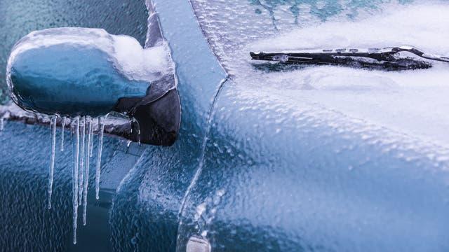 Eiskruste auf Außenspiegel und Scheibenwischer eines Autos