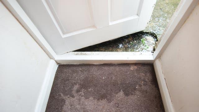 Wasser sickert durch einen Türrahmen auf den Teppich