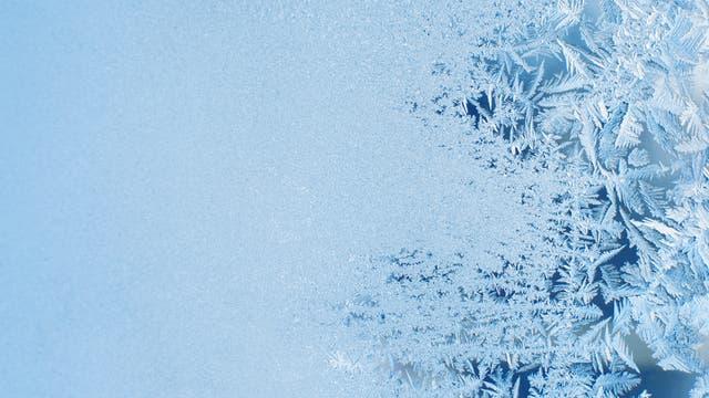 Eisschicht und Eisblumen am Fenster
