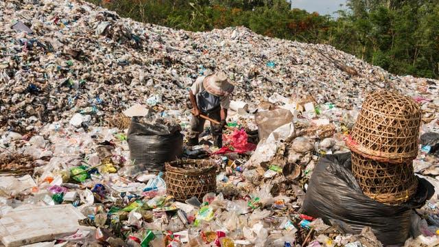 Ein Mann mit Strohhut durchforstet eine Mülldeponie