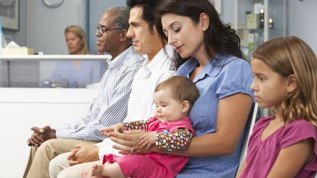 Zwei Männer, eine Frau und zwei Kinder, Im Hintergrund eine Sprechstundenhilfe