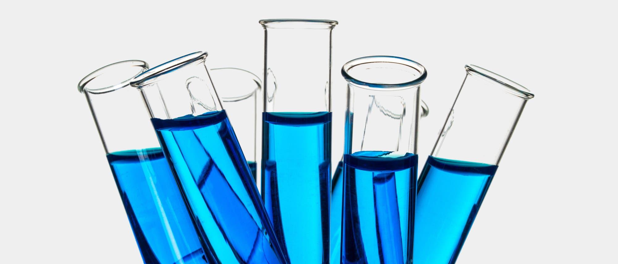 Reagenzgläser mit blauer Lösung in einem großen Becherglas