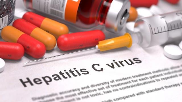 """Symbolbild mit Tabletten und Spritzen und einem Zettel, auf dem """"Hepatitis C Virus"""" steht."""