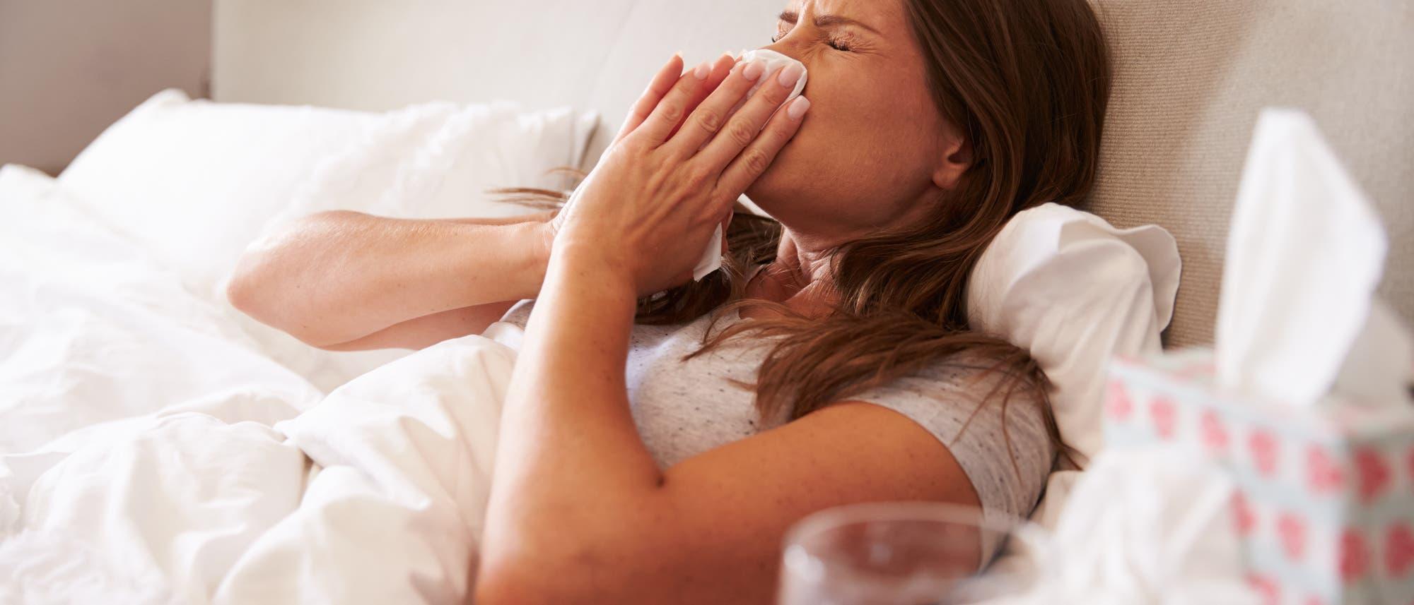 Eine junge Frau liegt in gesellschaft einer größeren Anzahl Taschentücher im Bett und schneuzt sich gerade die Nase