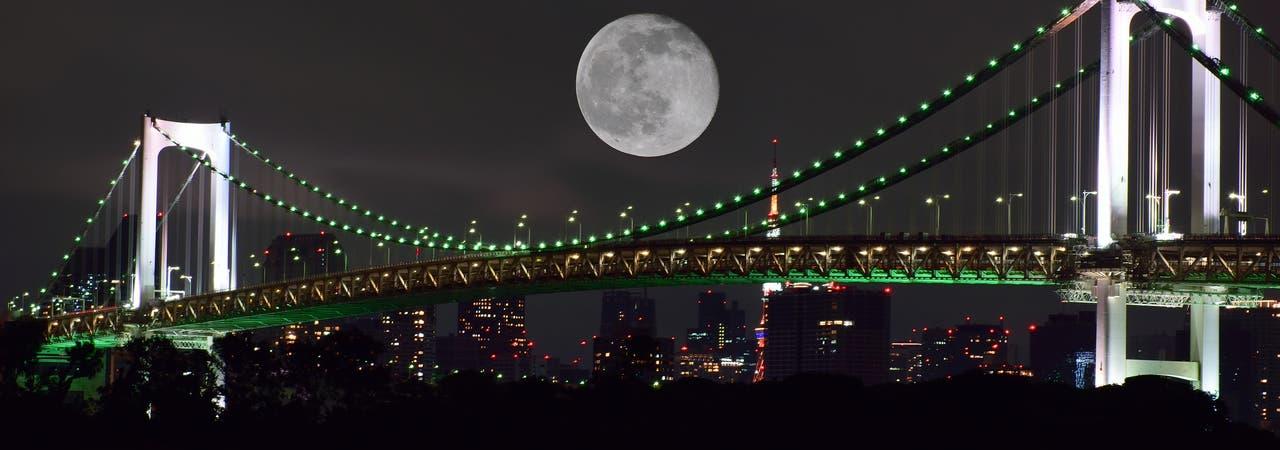 Mond über einer bunt beleuchteten Hängebrücke im Hafen von Tokio