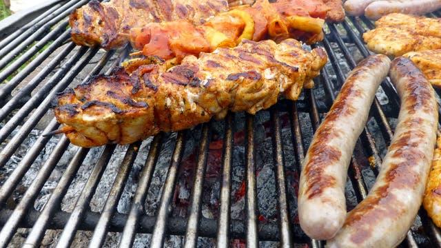 Fleischstücke und Wurst auf einen geringfügig versifften Grillrost