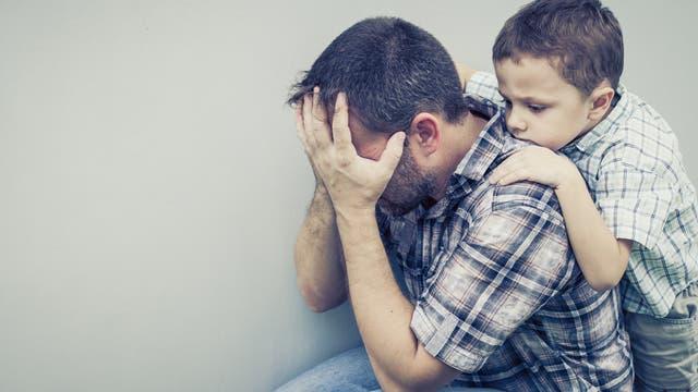 Vater und Sohn vor weißer Wand
