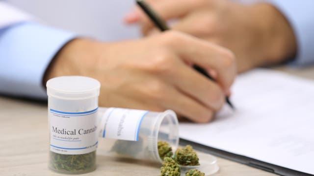 Zwei Pillendosen mit Grünzeug, dahinter füllt ein Arzt ein Rezept aus