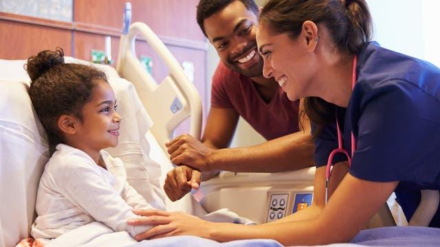 Lachendes Kind liegt im Krankenbett, Vater und Ärztin stehen daneben