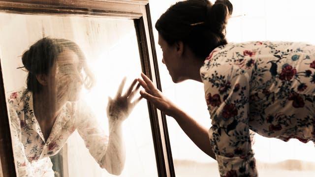Eine Frau kniet vor einem Spiegel und streckt die Hand nach ihrem Spiegelbild aus.