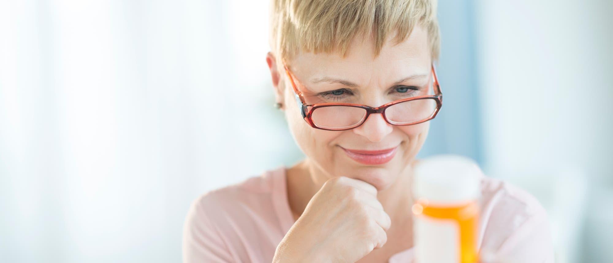 Eine Frau liest die Aufschrift auf einer Medikamentenpackung