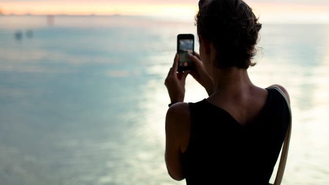 Frau macht Foto vom Sonnenuntergang