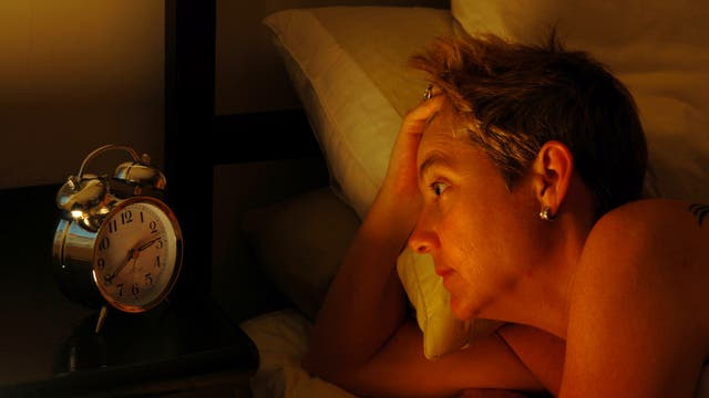 Frau kann nicht schlafen und starrt auf Wecker