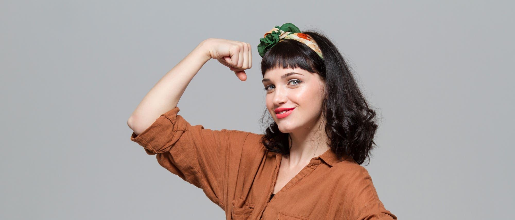 Eine Frau zeigt sich in typisch starker Pose und spannt scheinbar ihren Bizeps an.