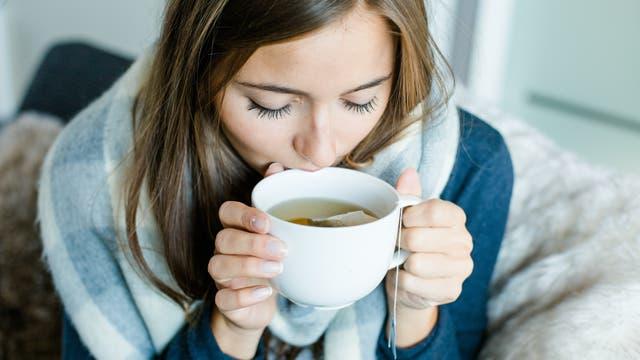 Kranke Frau sitzt auf dem Sofa und trinkt Tee