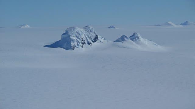 Bergspitzen ragen durch die antarktische Eiskappe.