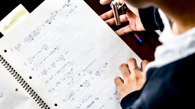 Eine Person löst mathematische Gleichungen