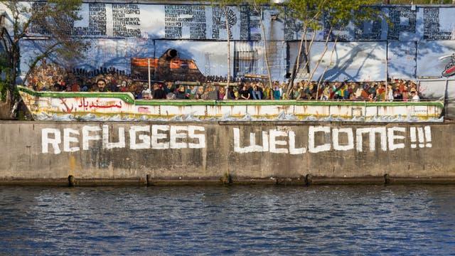 """Auf eine Mauer am Rand eines Flusses befindet sich ein Graffito """"Refugees Welcome""""."""