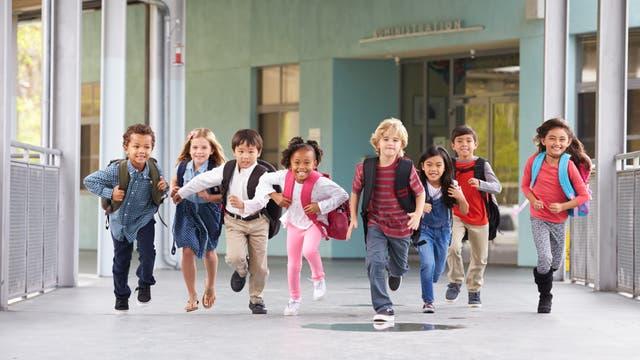 Grundschulkinder rennen über den Hof