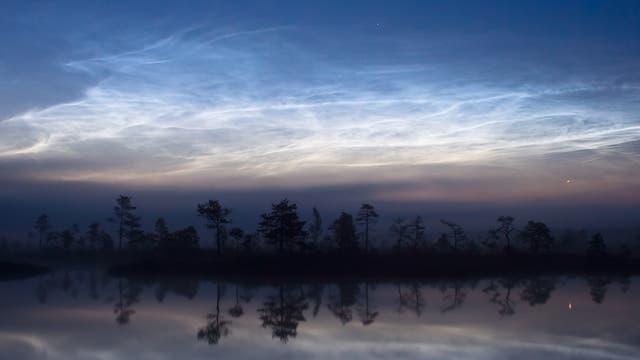 Leuchtende Nachtwolken über einem See