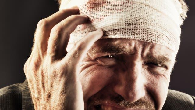 Ein Mann hält seinen verletzten Kopf und leidet
