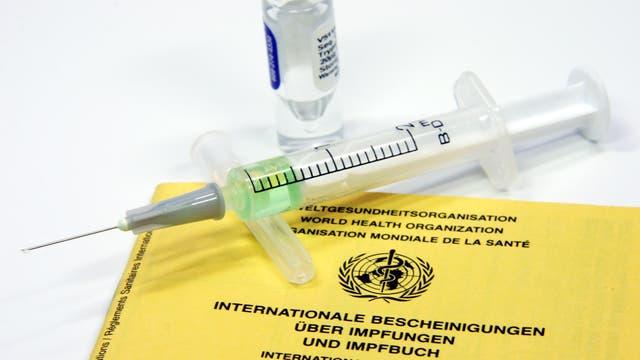 Spritze liegt auf Impfpass