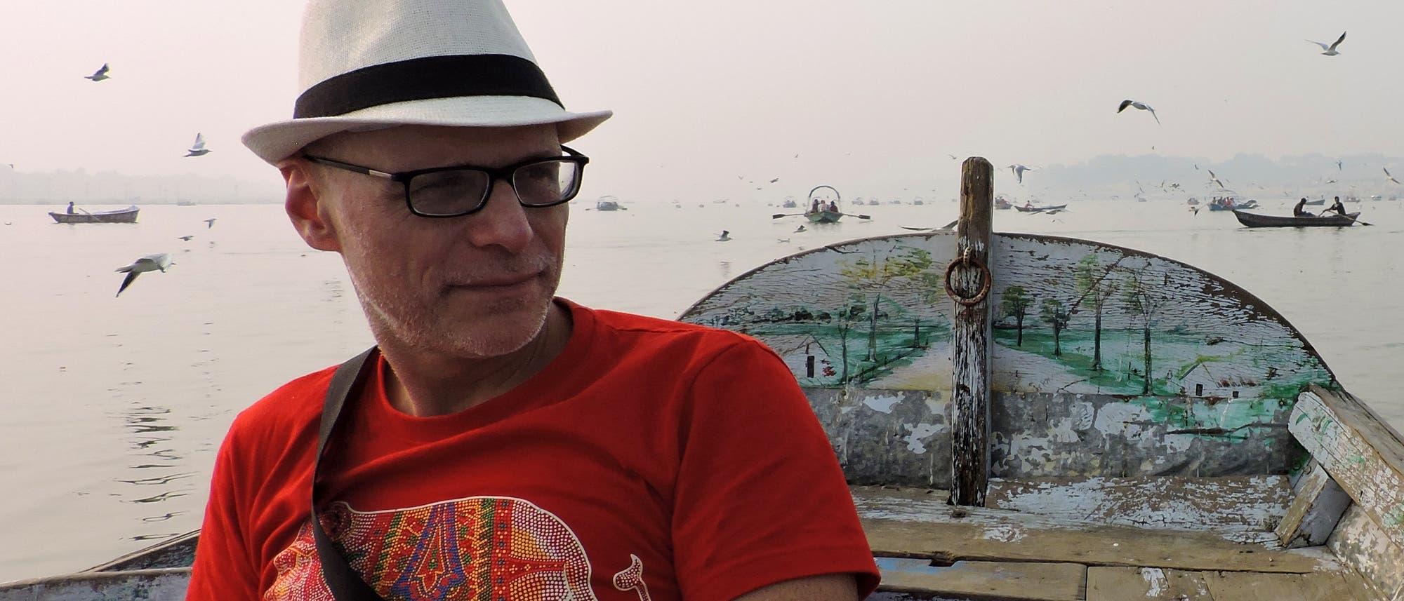 Der Psychologe Arne Dietrich sitzt auf einem Boot. Im Hintergrund sind weitere Boote und Vögel zu sehen.