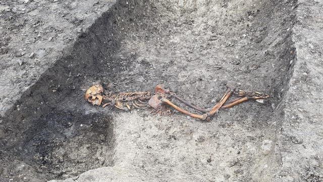 Skelett in einem Graben mit dem Gesicht nach unten und gefesselten Händen.