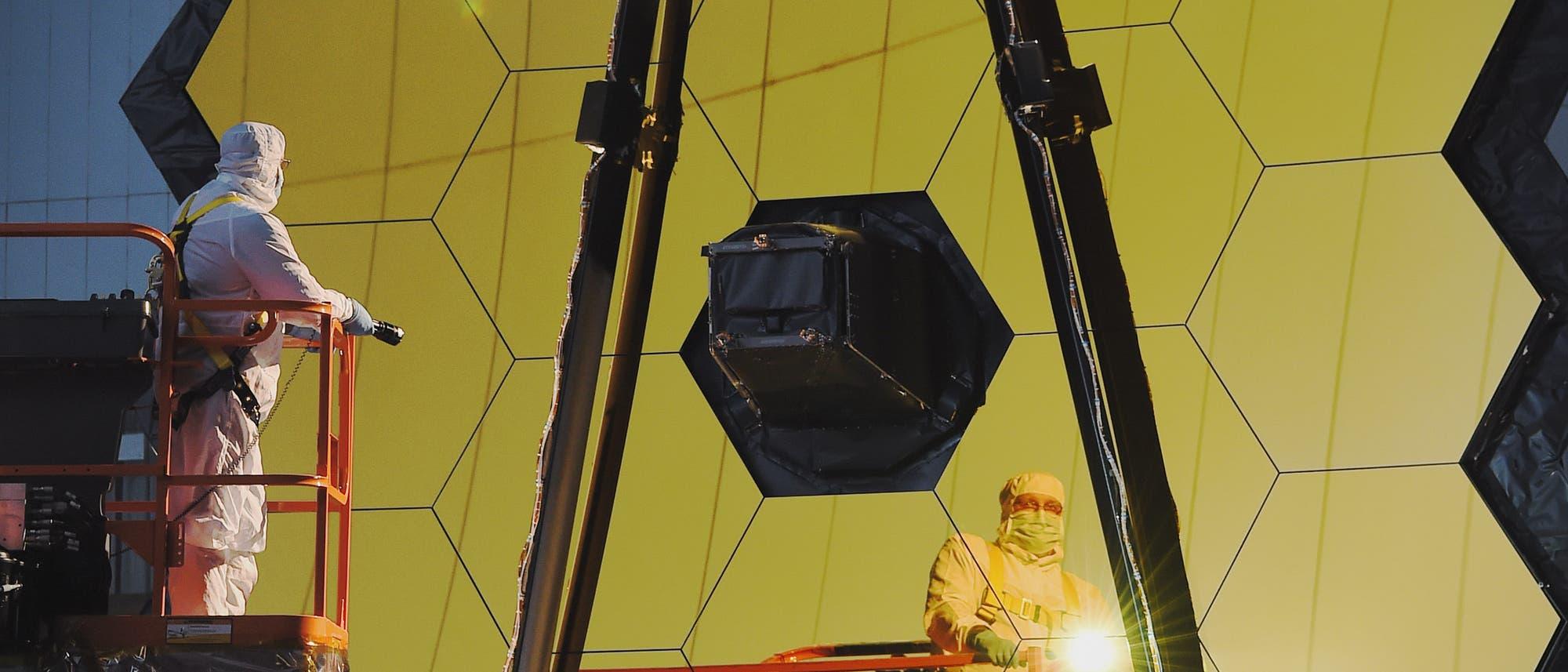 Das James Webb Space Telescope wird voraussichtlich im Oktober 2018 starten. Dieses Foto zeigt Arbeiten am goldenen Hauptspiegel des Teleskops im Reinraum am Goddard Space Flight Center der NASA.