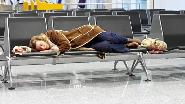 Eine Flugreisende schläft am Flughafen