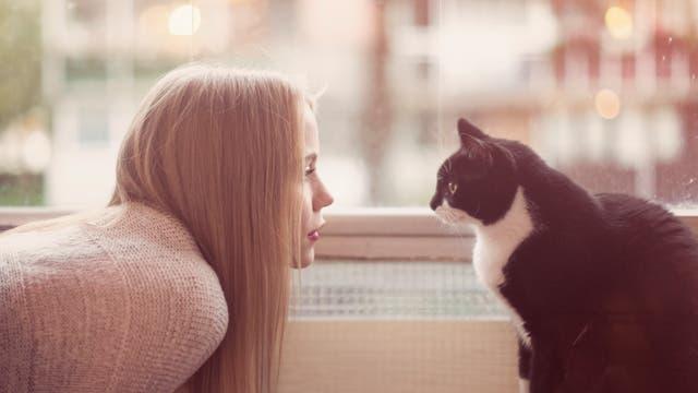 Frau sieht Katze in die Augen