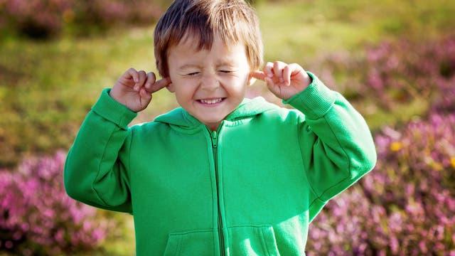 Kleiner Junge schützt seine Ohren