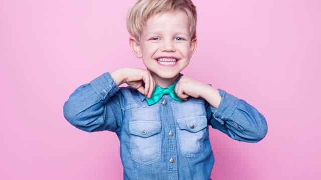 Ein Junge präsentiert stolz seine hellgrüne Fliege.