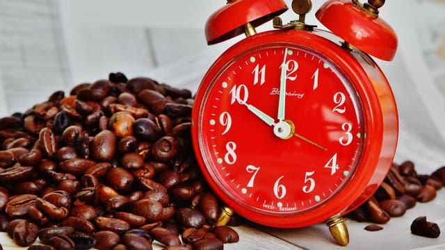 Kaffeebohnen und ein roter Wecker