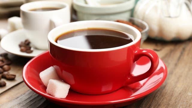 Tasse Kaffee mit zwei Würfeln Zucker